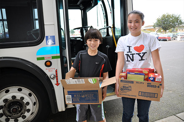 a boy and a girl stand outside a city bus holding boxes of food