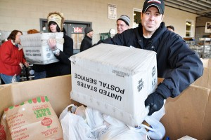 a postal drive volunteer dumps donated food into a tote