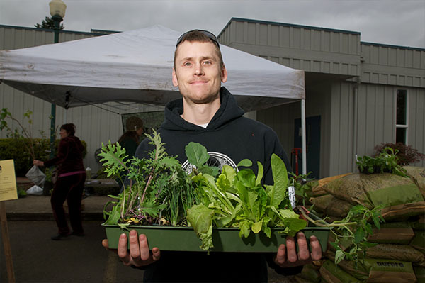 a man smiles on a grey day, holding a tray of plant starts