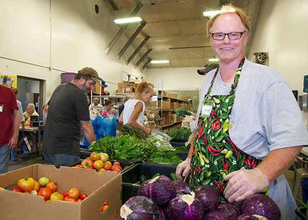 a man with red hair, glasses and a pepper apron stands by a pile of purple cabbage