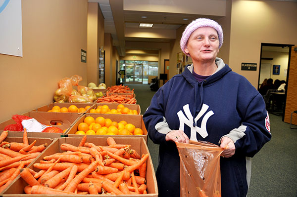 A woman with a pink hat fills a bag with vegetables next to a box of carrots
