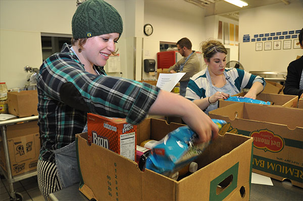 a young person sorts through food donations in a box