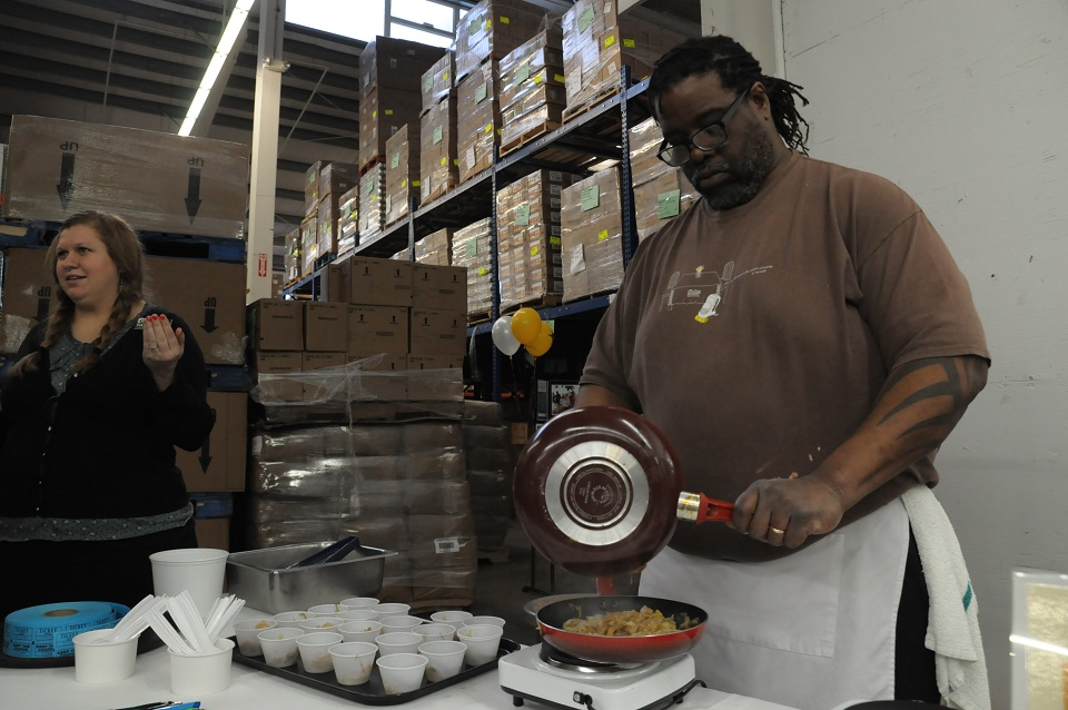 a tall african american man scrapes food from one pan to another.