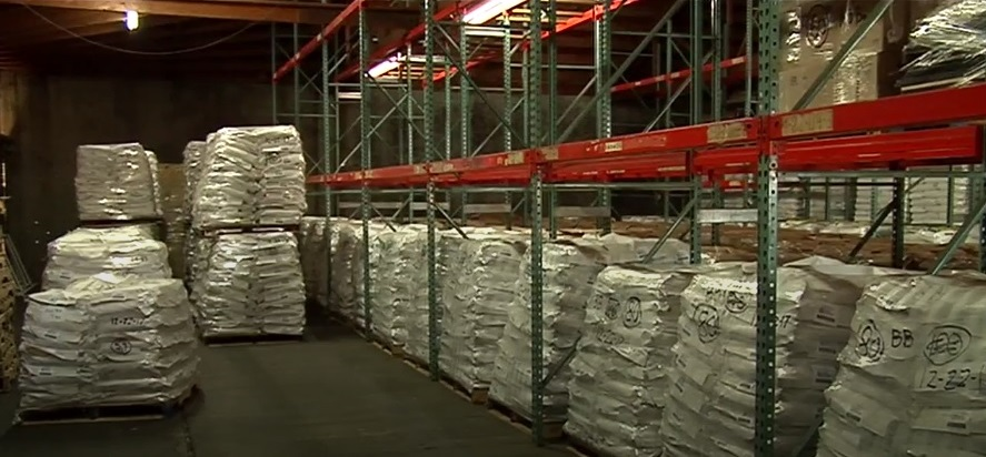 A warehouse full of large bags of black beans.