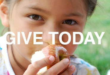 a young girl with brown hair eats an apple text says give today